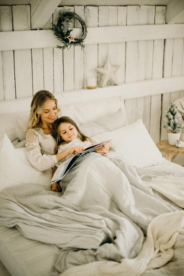 ベットの上でお母さんと女の子が一緒に絵本を読んでいる写真