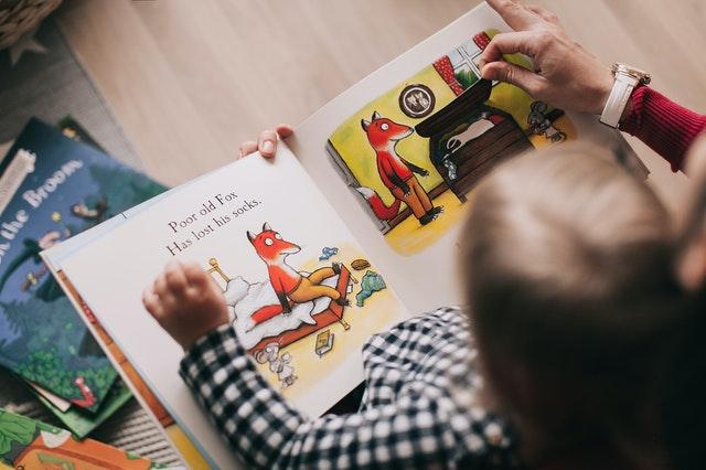 男の子がお父さんと一緒に仕掛け式の絵本を読んでいる写真