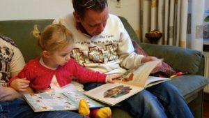 ソファーの上でお父さんと娘が絵本を読んでいる