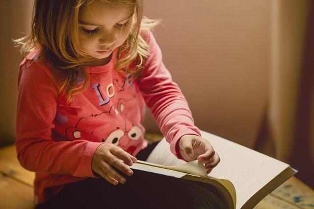 ピンクのロングTシャツを着て黒いズボンをはいている女の子が大きな本を読んでいる写真