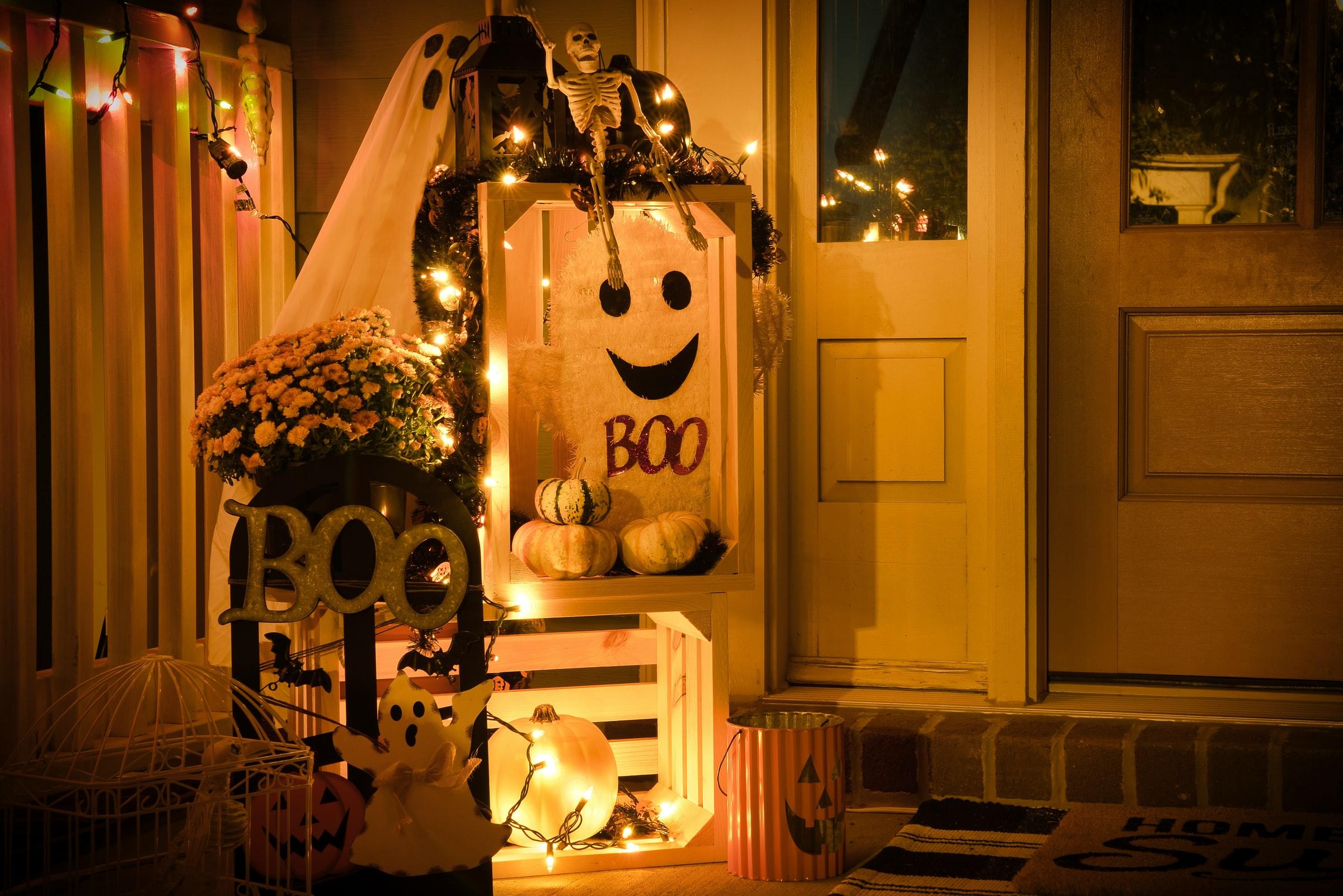 玄関のドアがライトアップされていて、お化けの置物やBOOと書かれた板でデコレーションしてある様子