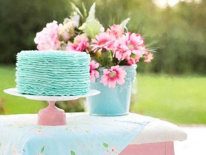 ピンクのテーブルの上に、ピンクのお花と水色のケーキがお皿に載っている写真