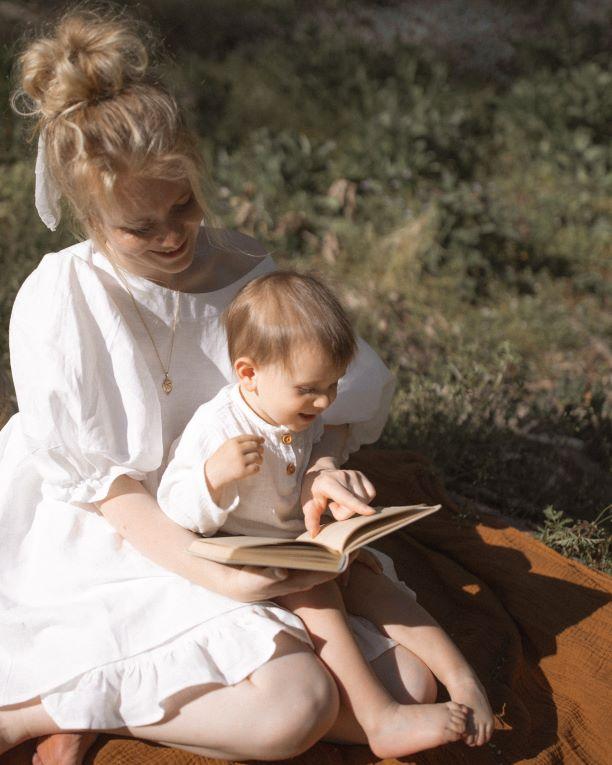 小さな男の子がお母さんの膝の上で絵本を楽しんでいる様子
