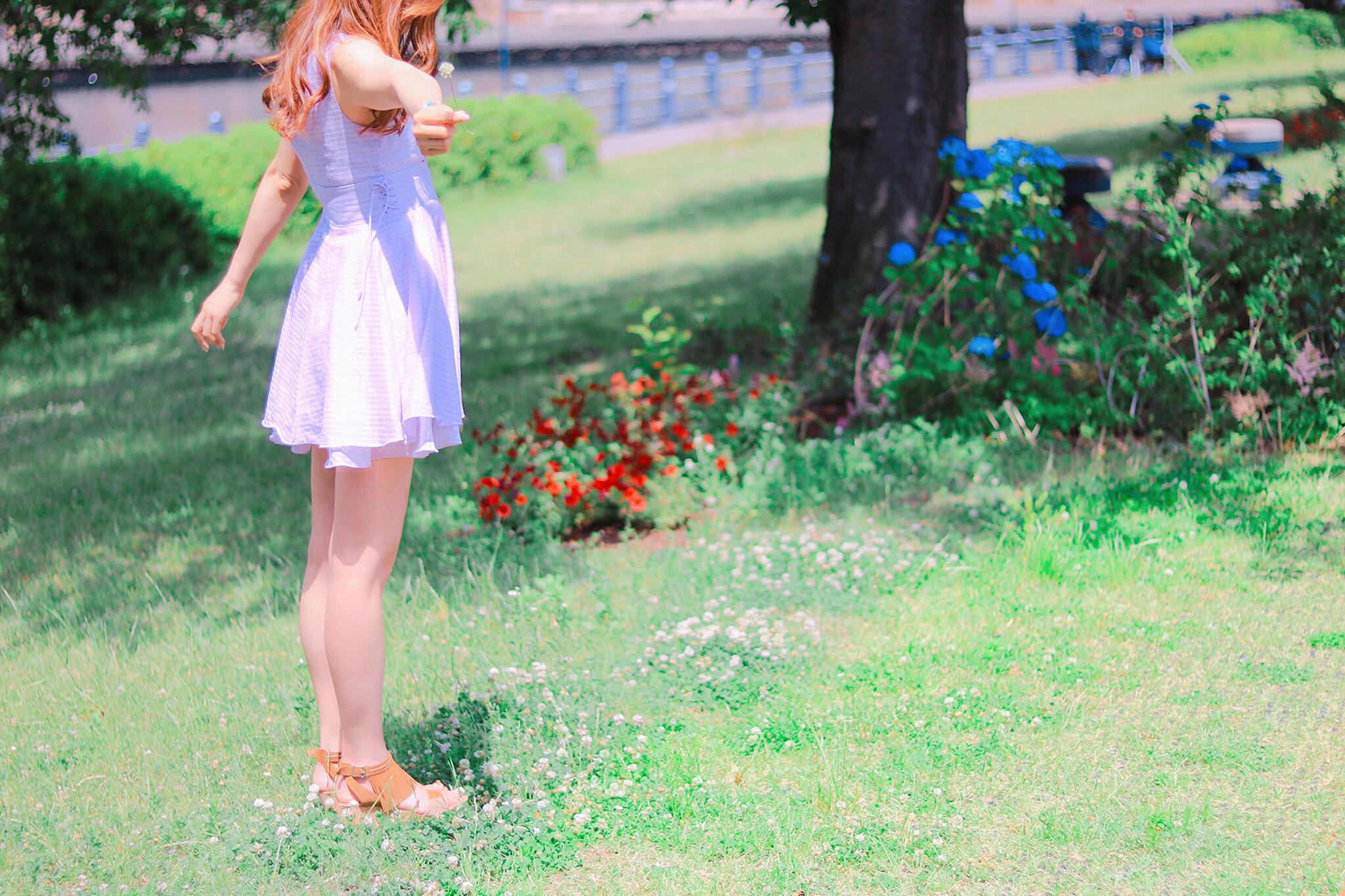芝生の上でノースリーブのワンピースを着た女の子がストレッチをしている写真