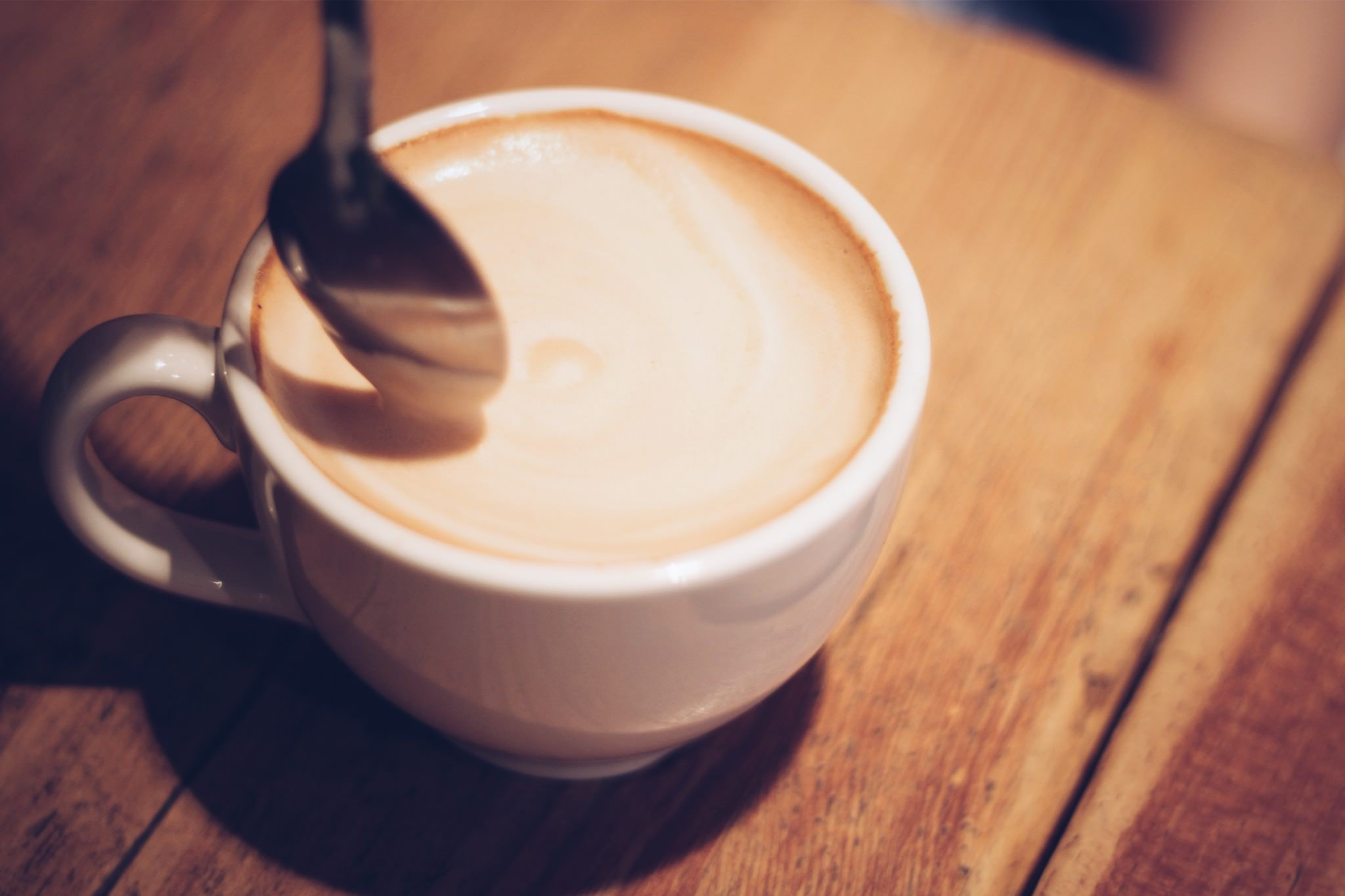 木製のテーブルの上の白いマグカップに入ったコーヒーミルクの写真