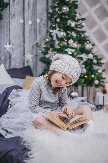 クリスマスツリーの横でニットの帽子をかぶった女の子が絵本を読んでいる写真
