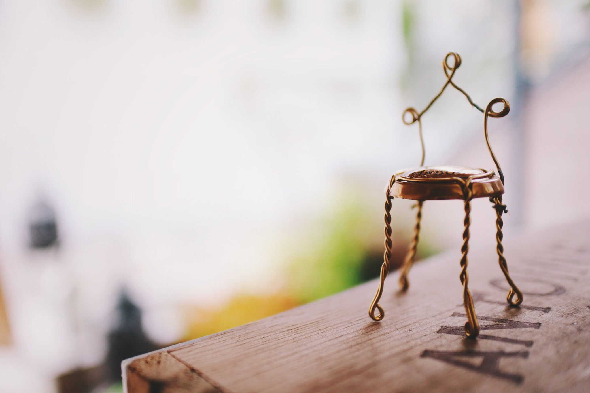 木製のテーブルの上に針金の小さな椅子の写真