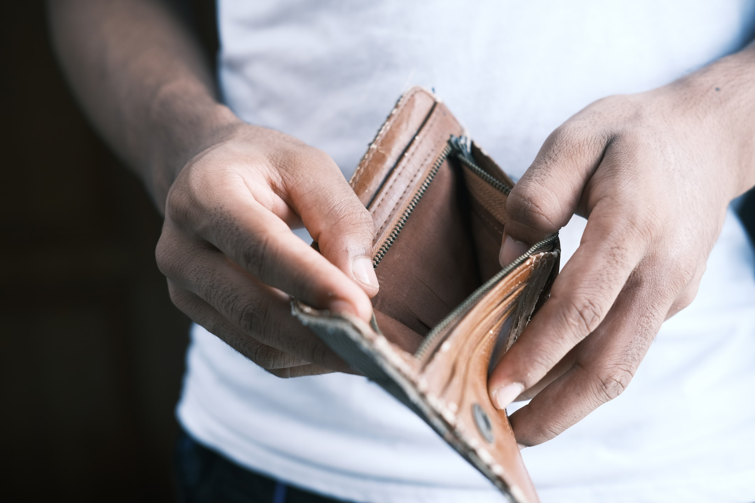 白いTシャツを着た男の人が空っぽの財布と開けている写真