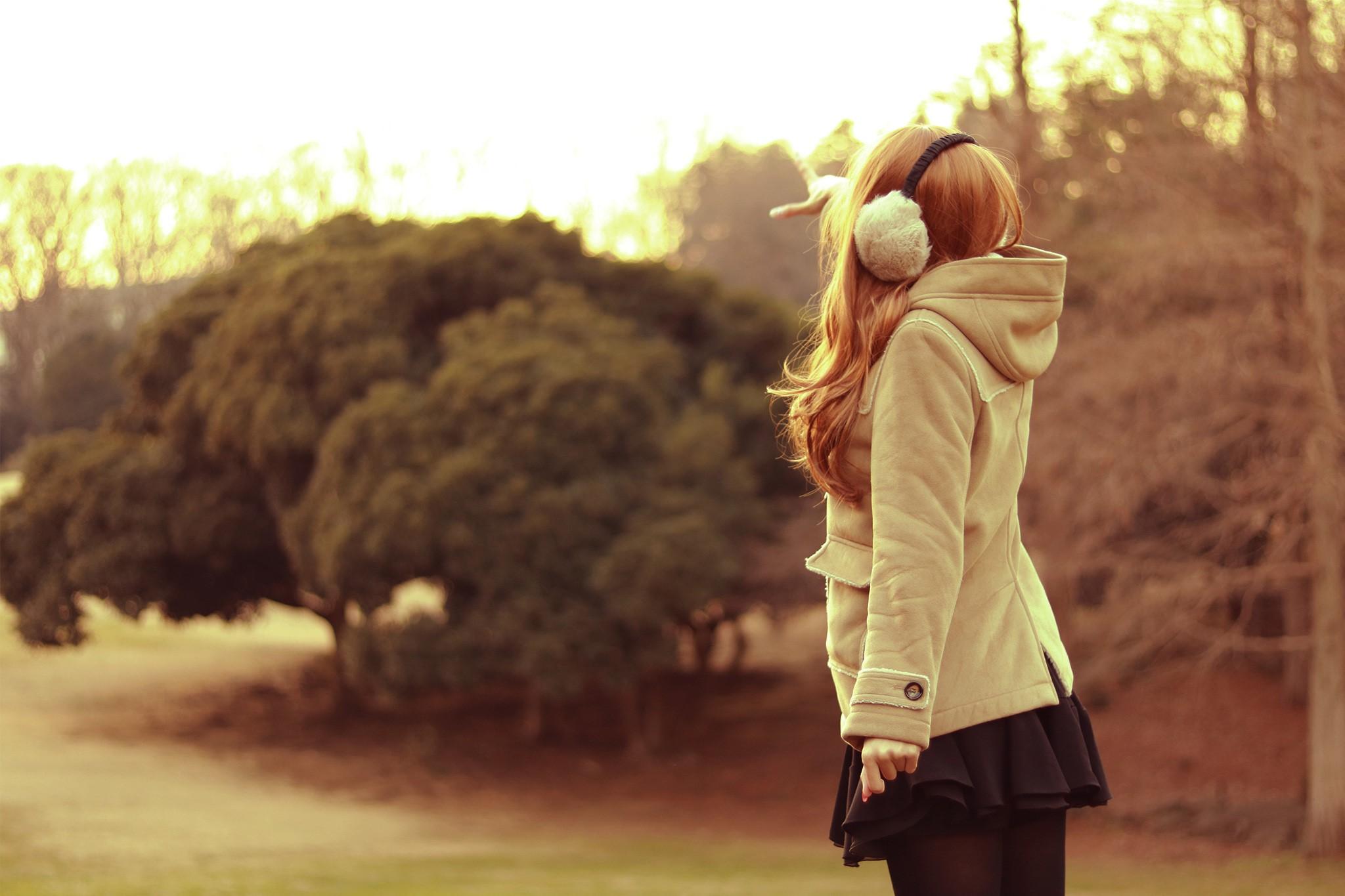 ベージュのダッフルコートと黒いミニスカートを着た女の子が、向こうを指さしている写真