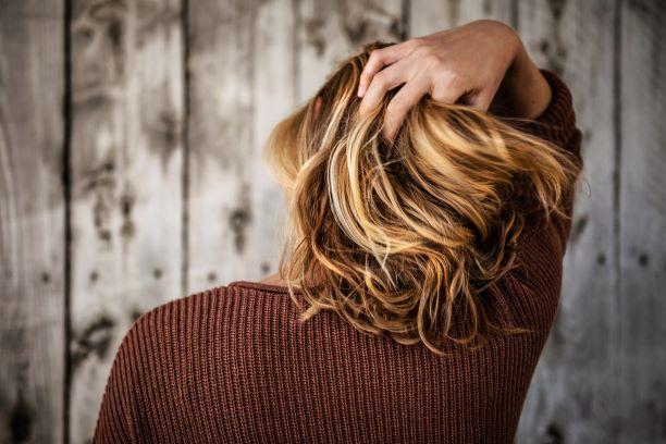 ブロンドの髪の女性が髪をかき上げている写真