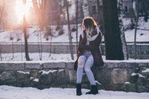 寒い雪の外で、コートを着た女の人が寒がっている写真