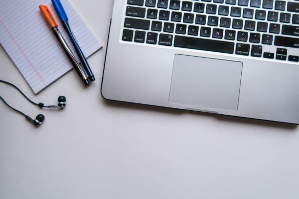 ノートパソコンの横にメモ帳とイヤホンと赤と青のボールペンがある写真