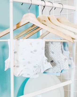 ハンガーに赤ちゃんの洋服を掛けて、室内で干している写真