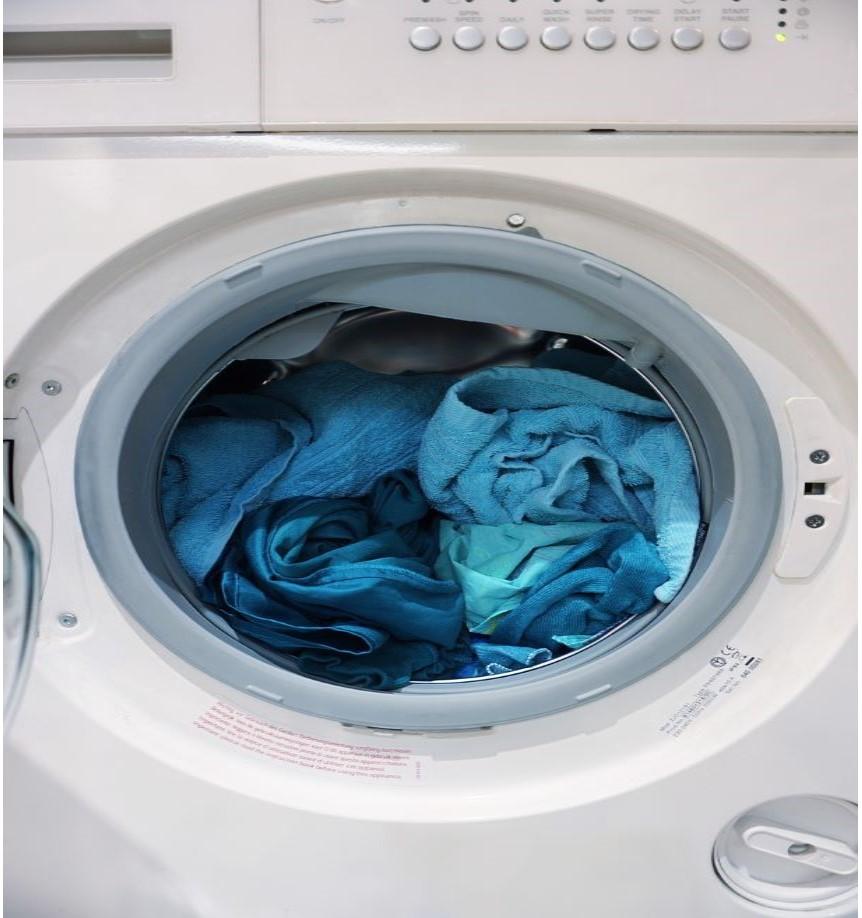 白い洗濯機の中に、青や水色の衣類が入っている写真
