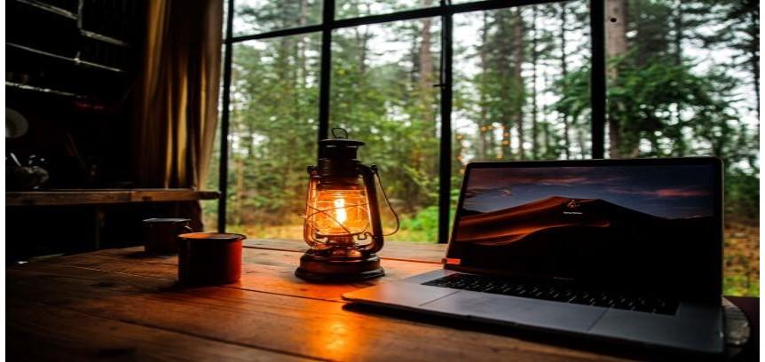 コテージの机の上にランプとノートパソコンがある写真