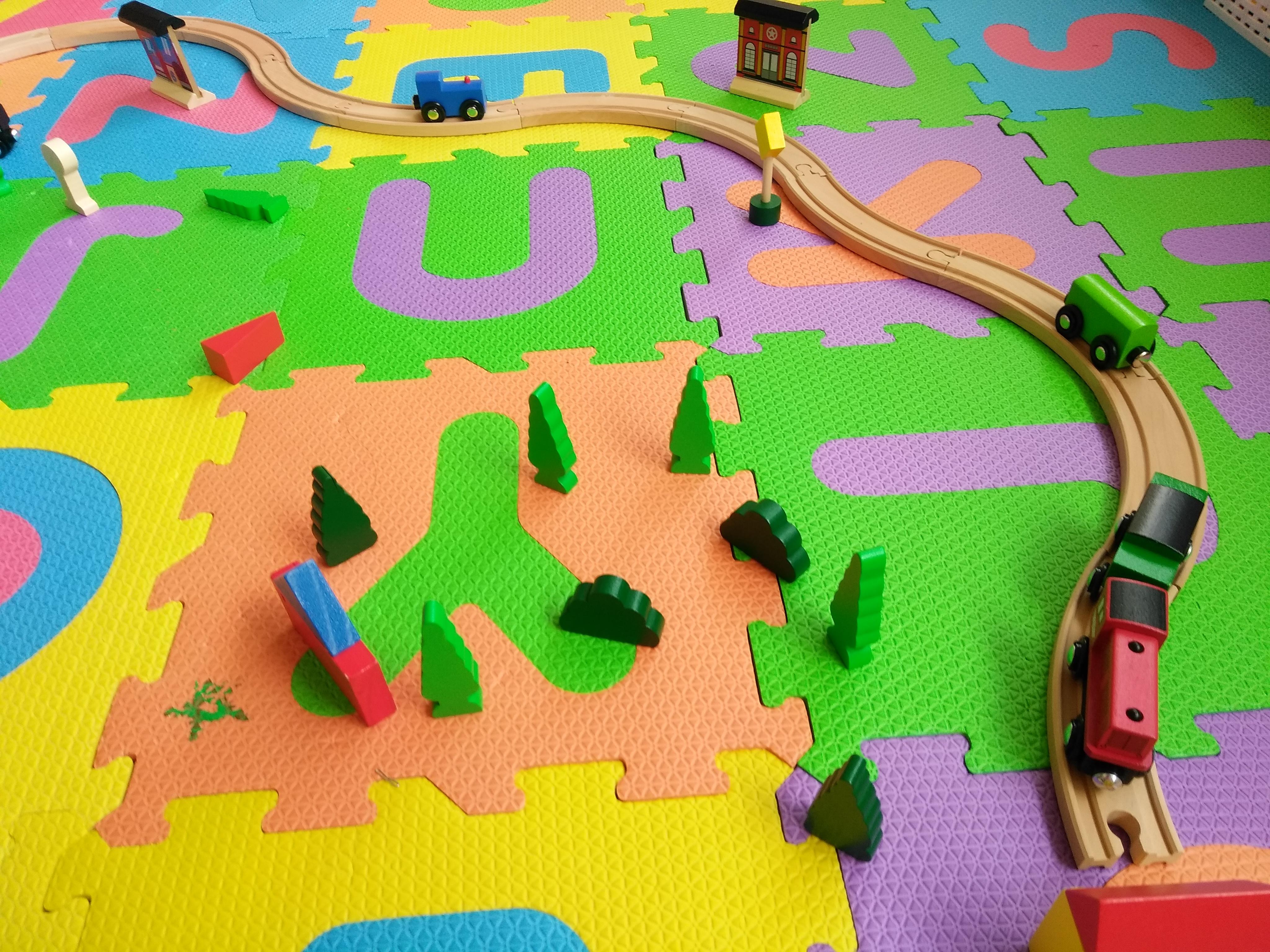 おもちゃの木製のレールの上におもちゃの電車が走っている写真