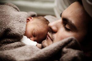 パパが産まれたての赤ちゃんを胸に置いて寝かせている写真