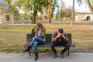 ベンチに座っている男女。男性が頭を抱え、女性がそっぽ剥いている