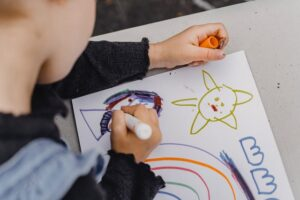 子供が机の上でお絵描きしている様子