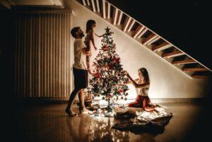 パパとママと娘でクリスマスツリーの飾りつけをしている様子
