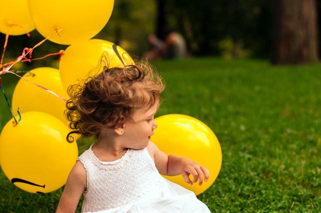 黄色の風船を沢山持って女の子が、芝生の上で座っている