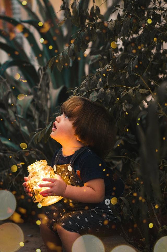 小さな男の子が大きな緑の植物の隣に座って瓶に入った灯りを持っていて、その灯りが植物に灯りを照らされているのを男の子が不思議そうに見ている様子