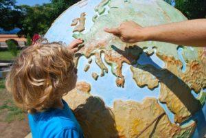 子供と大人が大きな地球儀を見ている写真