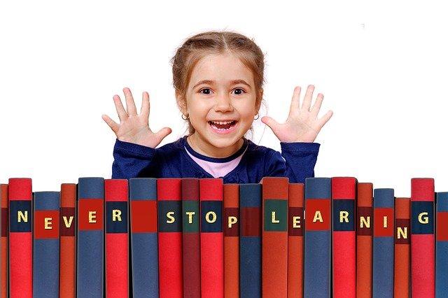 女の子が沢山の本の前で両手をあげている写真