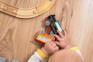 ハイハイしている赤ちゃんが、木製の電車のレールと電車のおもちゃで遊んでいる写真