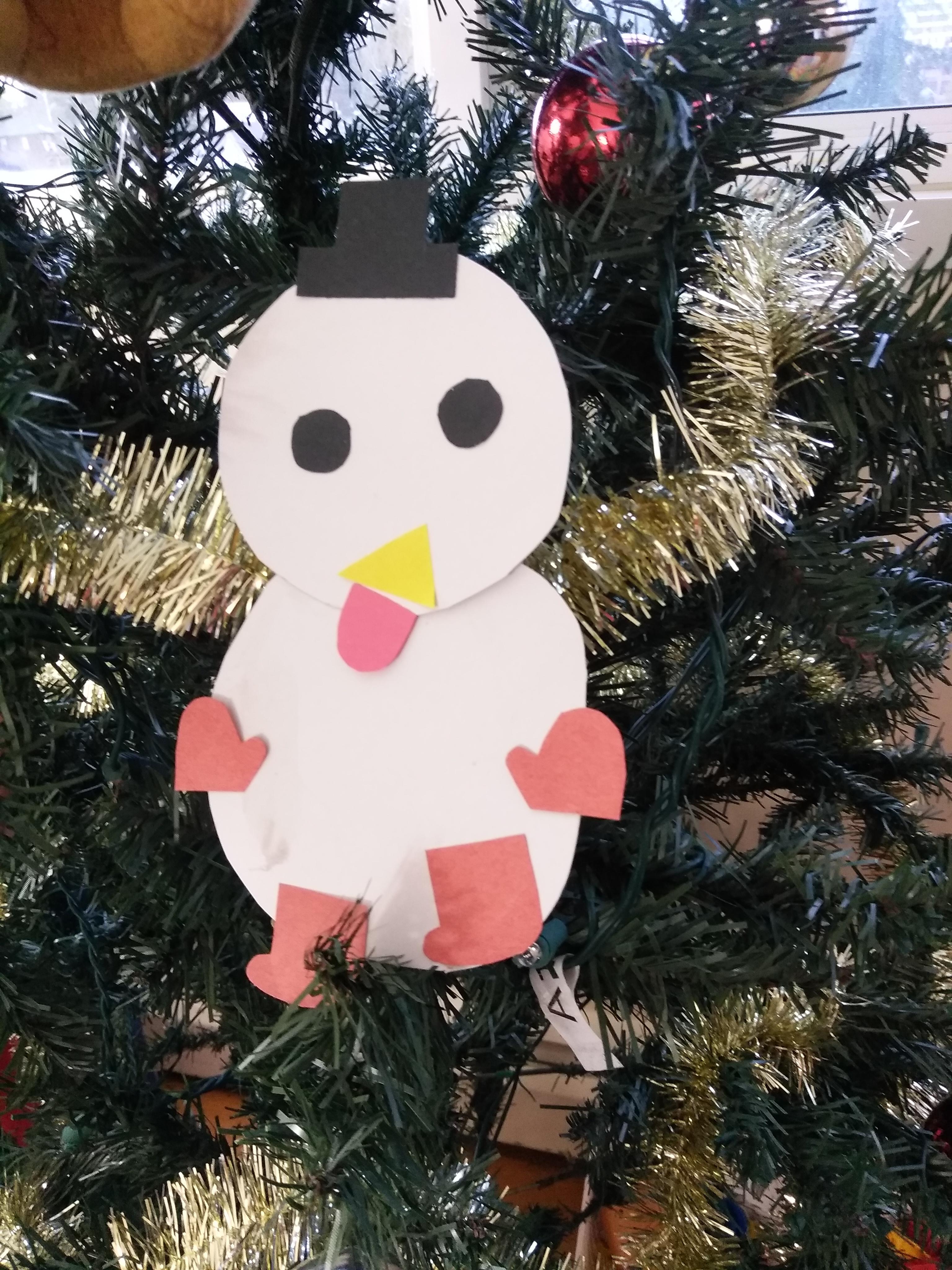 娘が作った雪だるまのクラフトをツリーに飾っている写真