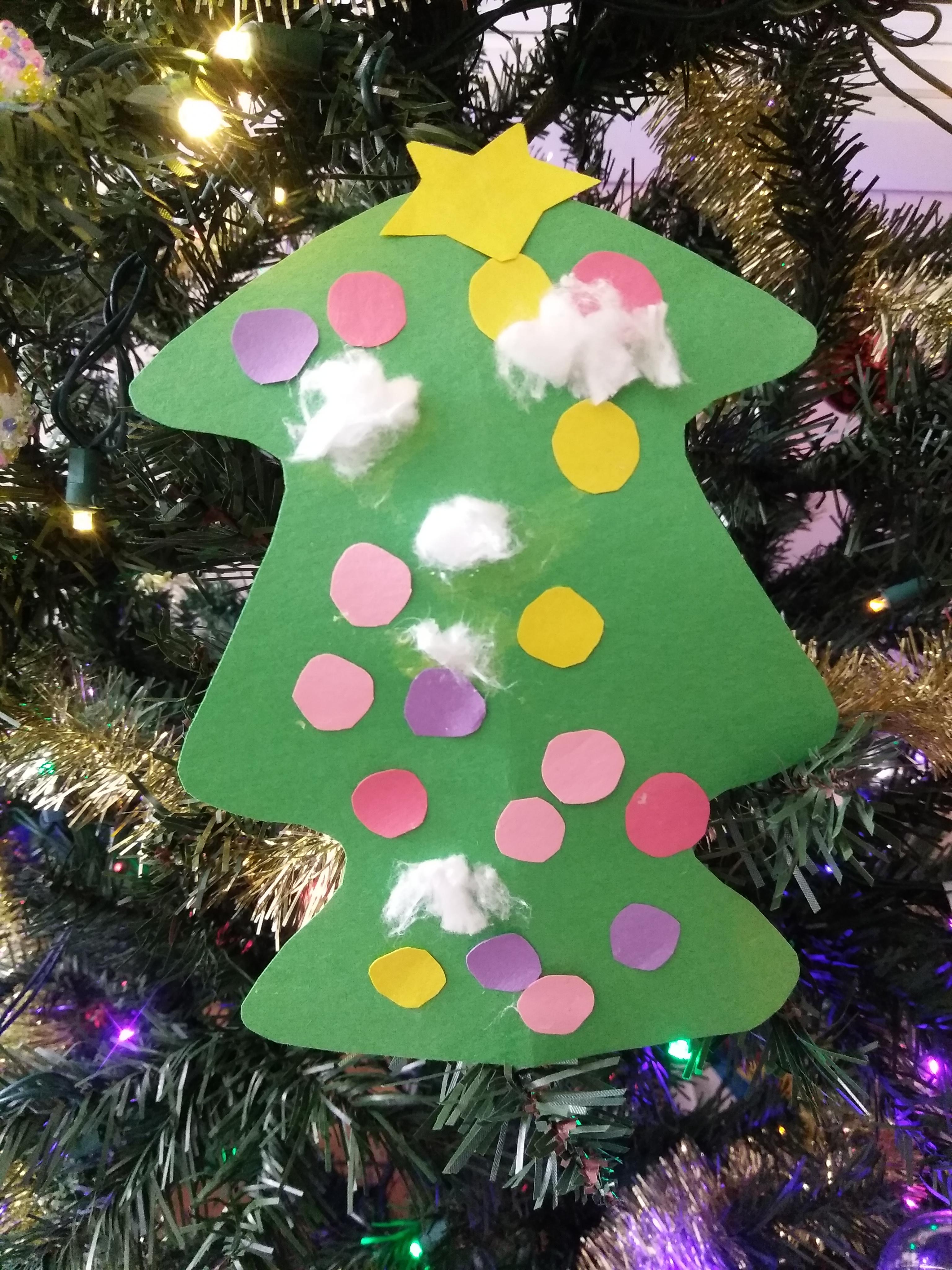 クリスマスツリーのクラフトにコットンを貼ったのをクリスマスツリーに飾っている写真