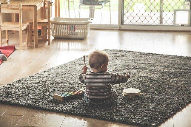 赤ちゃんがグレーのマットの上で木琴とタンバリンを叩いて遊んでいる様子