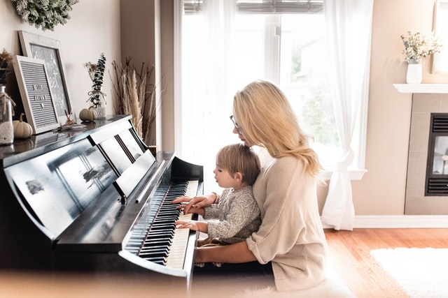 母親と男の子が一緒にピアノを弾いている様子