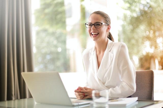 白いシャツを着たきれいな金髪の女性がパソコンの前で笑顔で笑っている様子