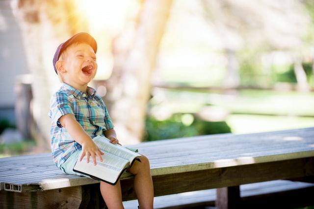 帽子を被った男の子が手すりに座って本を読んで笑っている