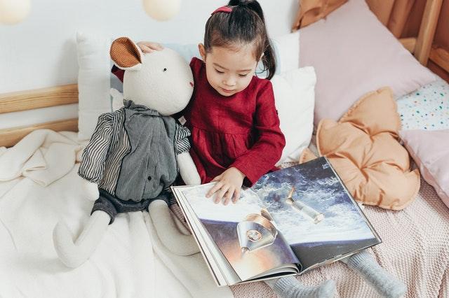 女の子がベットの上でぬいぐるみを抱えながら絵本を読んでいる写真