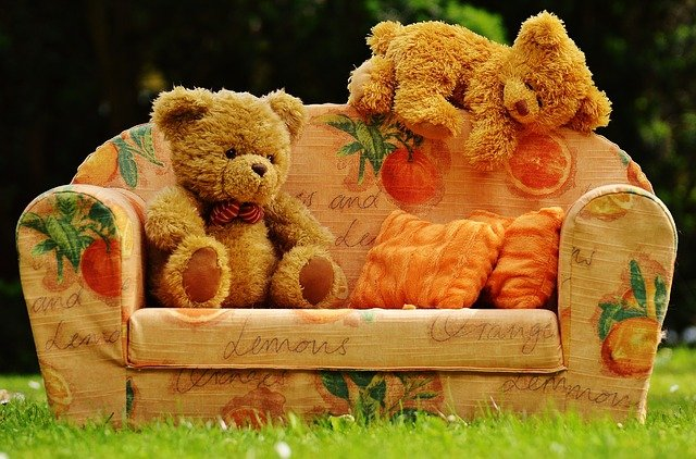オレンジ色の子供用のソファーに1匹のテディベアが座っていて、もう1匹がソファーに上っている写真