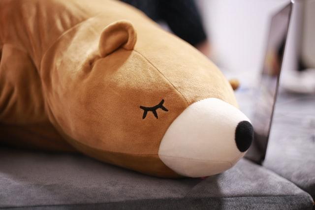 クマのぬいぐるみがソファーの上で眠っている写真