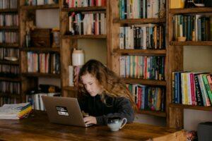 ブロンドの女の子が図書館でイヤホンをしながらパソコンを見ている様子