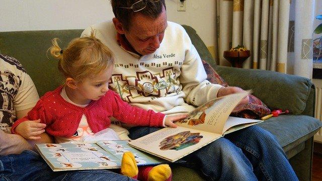 女の子がソファーの上でパパと絵本を読んでいる写真