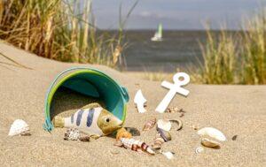 砂浜にバケツやおもちゃの魚、貝殻などが落ちている様子