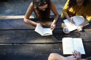 3人の女学生がテラスでドリンクを飲みながら本を読んで勉強をしている様子