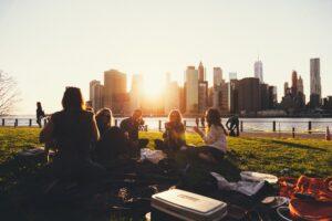 夕日を背中に5人の男女の学生が芝生の上で話をしている