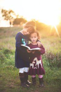 二人の姉妹が肩を組んで一緒に本を読んでいる様子