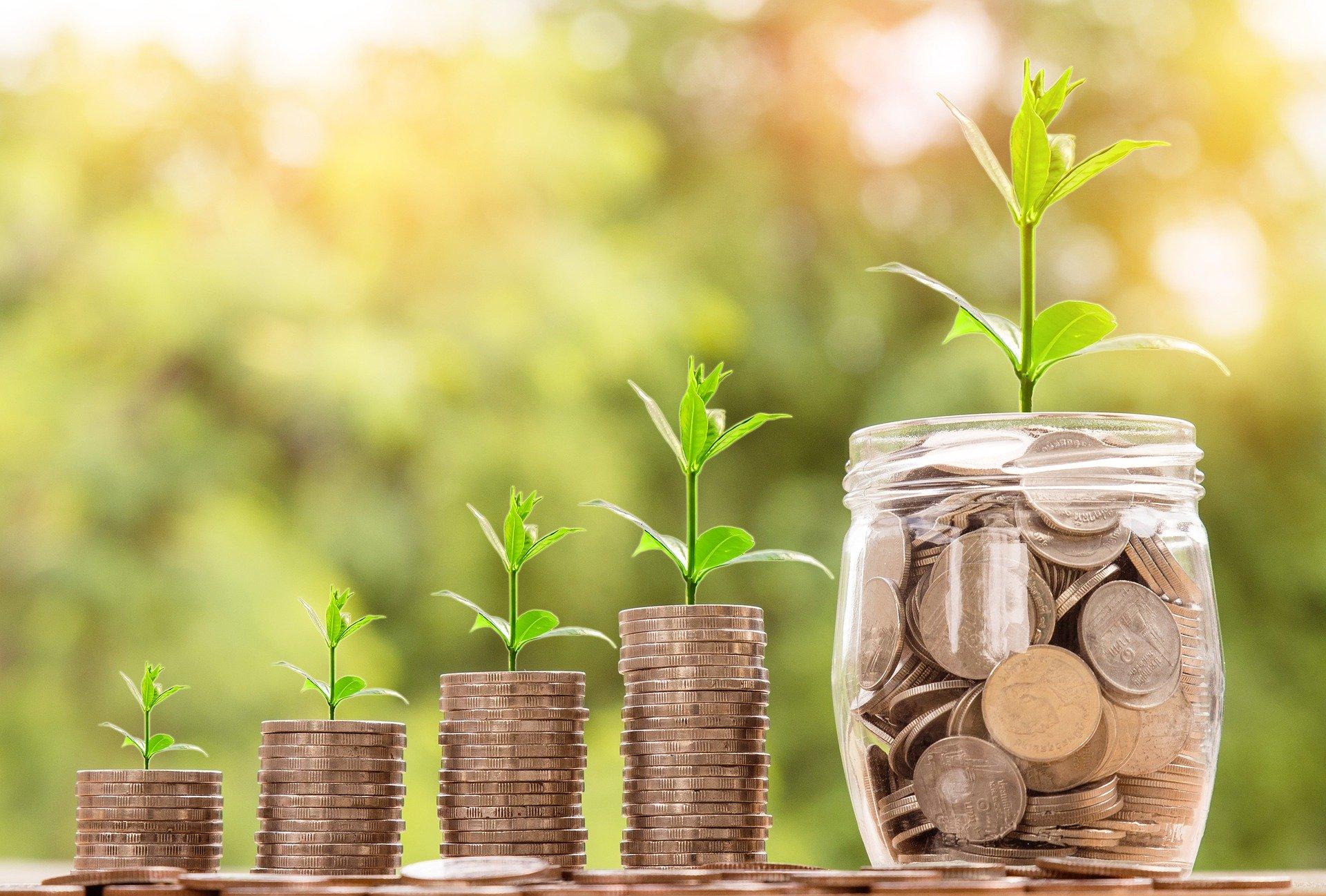 お金のコインが積み上げられていて、低・中・高と三段階に積み上げられている。一番右に沢山コインのお金の入った瓶がおいてある