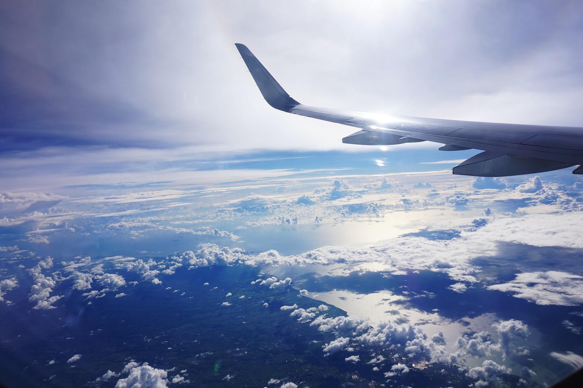 雲の上を飛んでいる飛行機の翼の写真