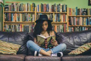 黒い帽子をかぶった若い女の人がソファーの上で本を読んでいる様子