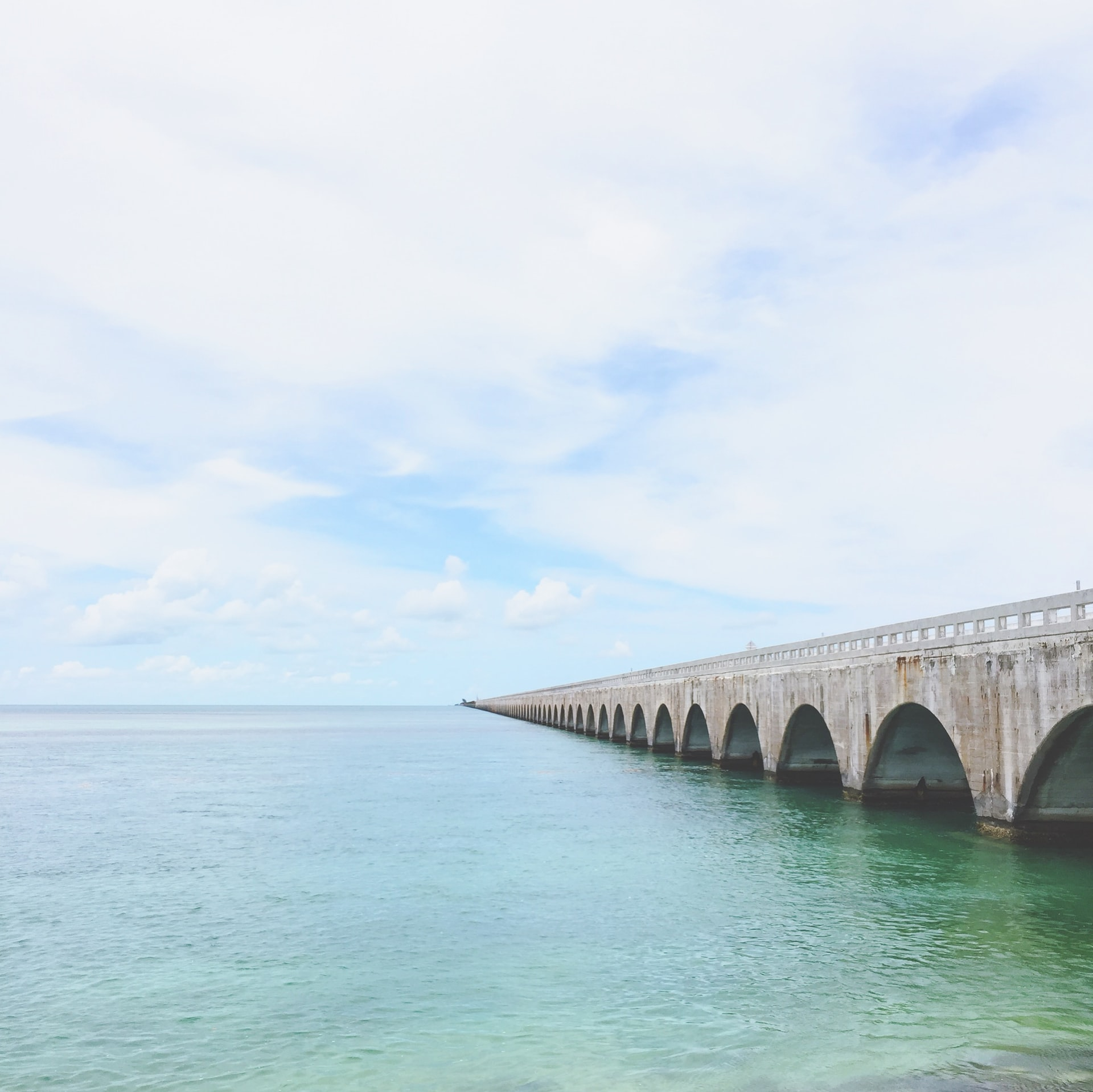どこまでも続くエメラルドグリーンの海とコンクリートの橋