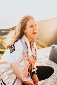 金髪でロングヘアの女性が草原で笑っている写真